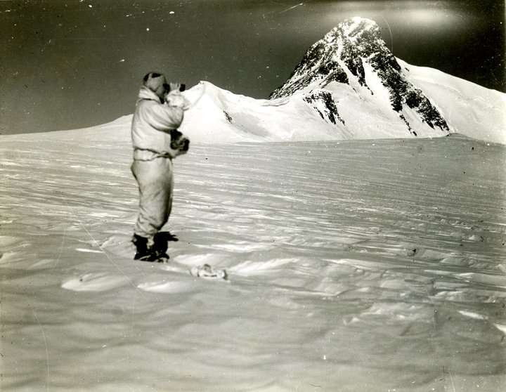 Person standing in snow with mountain in background