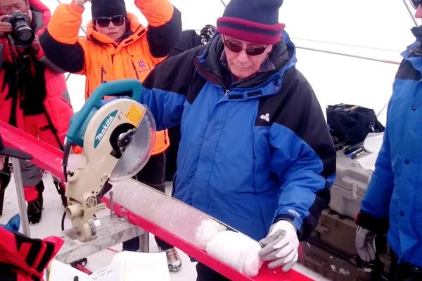 Lonnie using a saw to cut an ice core