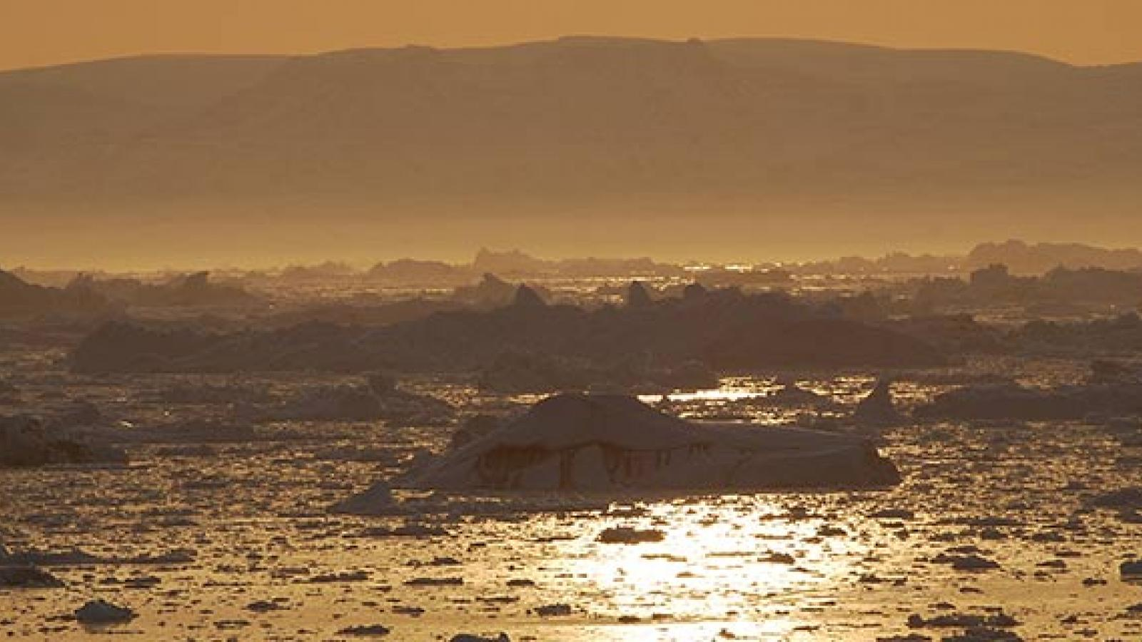 Sunset over icebergs in Disko Bay, Greenland.